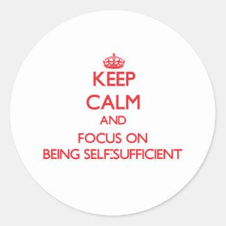 Guarde la calma y el foco en ser autosuficiente etiquetas redondas