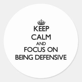 Guarde la calma y el foco en ser defensivo etiqueta redonda
