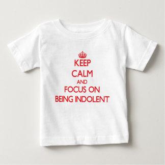 Guarde la calma y el foco en ser indolente t-shirts