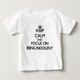 Guarde la calma y el foco en ser indolente tshirts