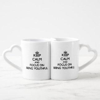 Guarde la calma y el foco en ser joven tazas para parejas