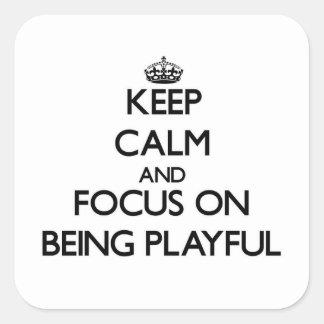 Guarde la calma y el foco en ser juguetón pegatinas cuadradases