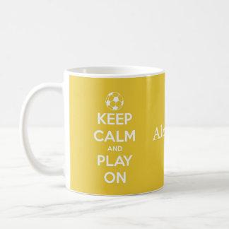 Guarde la calma y el juego en fútbol amarillo y taza