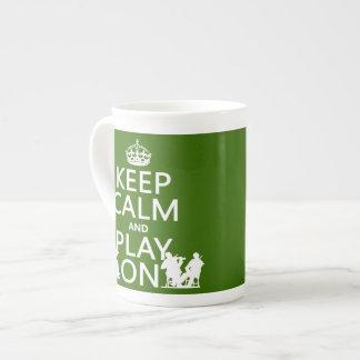 Guarde la calma y el juego en (los instrumentos at taza de porcelana