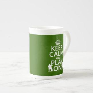 Guarde la calma y el juego en (los instrumentos taza de porcelana