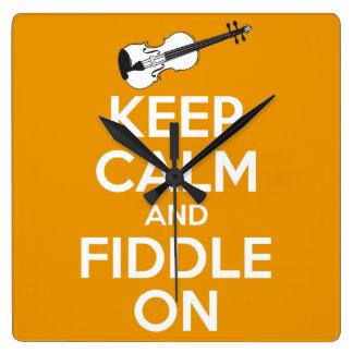 Guarde la calma y el violín en el naranja reloj cuadrado