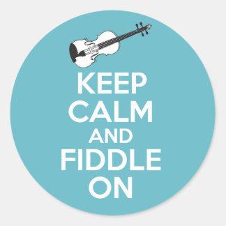 Guarde la calma y el violín en el violín en azul pegatina redonda