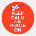 Guarde la calma y el violín en el violín en rojo etiqueta redonda