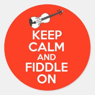 Guarde la calma y el violín en el violín en rojo pegatina redonda