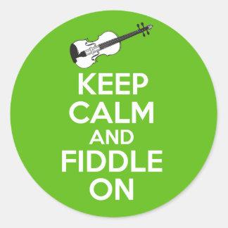 Guarde la calma y el violín en el violín en verde pegatina redonda