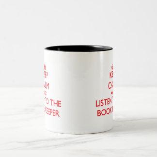 Guarde la calma y escuche el encargado de libro taza de café de dos colores