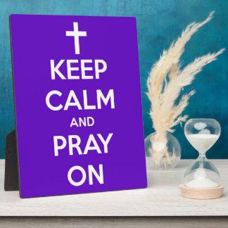 Guarde la calma y ruegue en placa púrpura