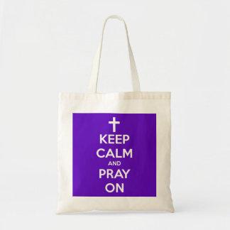Guarde la calma y ruegue en púrpura bolsa