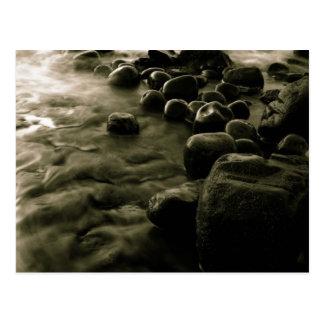 Guijarros blancos y negros cerca del agua postal