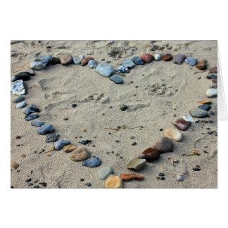 Guijarros del corazón en la arena tarjeta pequeña