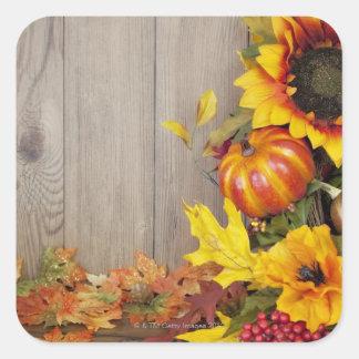 Guirnalda y hojas del otoño en el fondo de madera pegatina cuadrada
