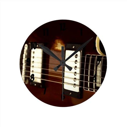guitar brown electric strings and bridge close up. clock
