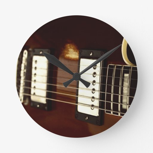 guitar brown electric strings and bridge close up. round clock