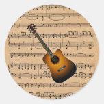 Guitarra acústica con el fondo de la partitura pegatina redonda