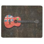 Guitarra acústica rasguñada y llevada de la bander cuadernos grapados