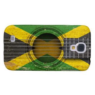 Guitarra acústica vieja con la bandera jamaicana