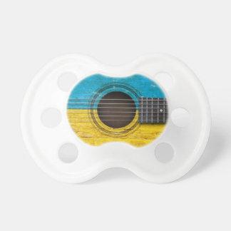 Guitarra acústica vieja con la bandera ucraniana chupete