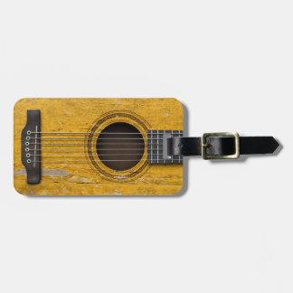 Guitarra acústica vieja envejecida y llevada etiqueta de maleta