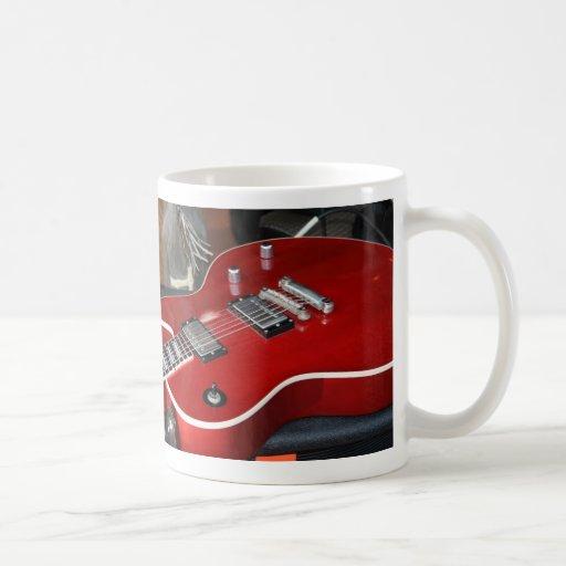 Guitarra roja en el amperio tazas