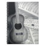 Guitarra y cuaderno espiral de la partitura