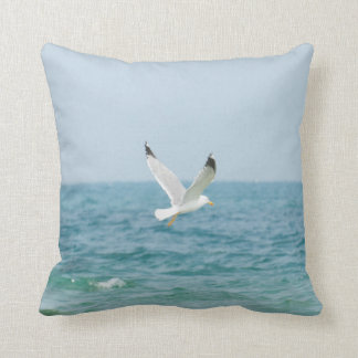 Gull flying above sea throw pillow