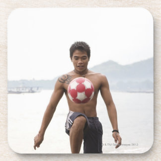 Guy playing football on beach coaster