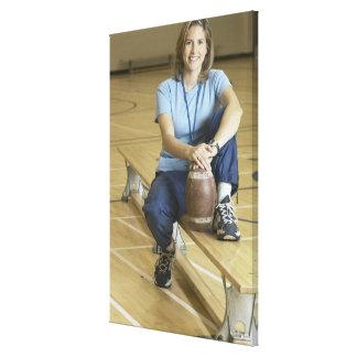 Gym teacher sitting on bench in gym canvas prints