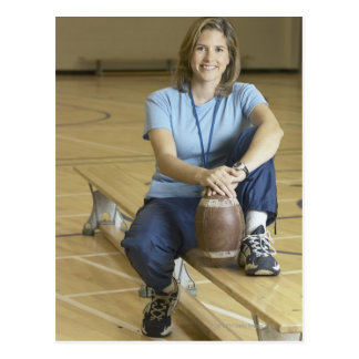Gym teacher sitting on bench in gym postcard