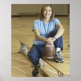Gym teacher sitting on bench in gym poster