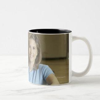 Gym teacher sitting on bench in gym Two-Tone coffee mug