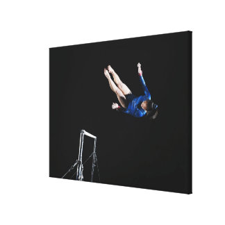 Gymnast (16-17) dismounting uneven bars canvas print