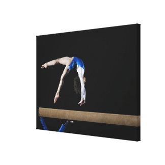 Gymnast (9-10) flipping on balance beam, side canvas print