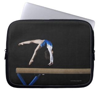 Gymnast (9-10) flipping on balance beam, side computer sleeve