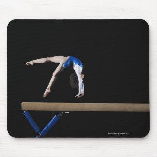 Gymnast (9-10) flipping on balance beam, side mouse pad