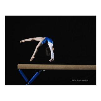 Gymnast (9-10) flipping on balance beam, side post card