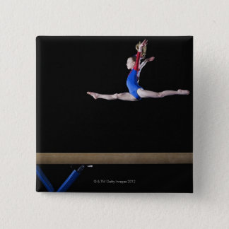 Gymnast (9-10) leaping on balance beam 2 button