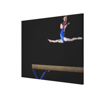 Gymnast (9-10) leaping on balance beam 2 canvas print