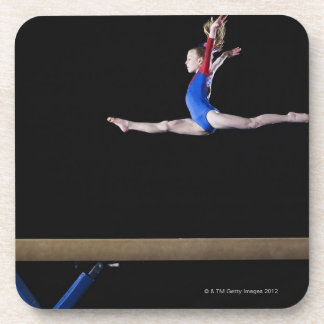 Gymnast (9-10) leaping on balance beam 2 drink coasters
