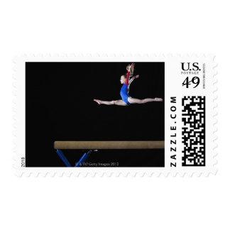 Gymnast (9-10) leaping on balance beam 2 postage