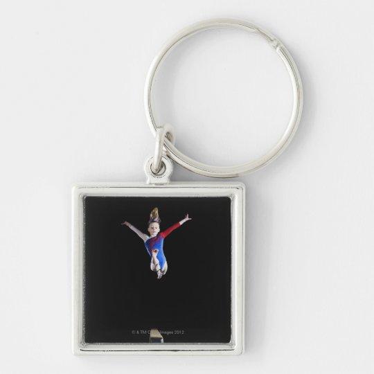 Gymnast (9-10) leaping on balance beam keychain