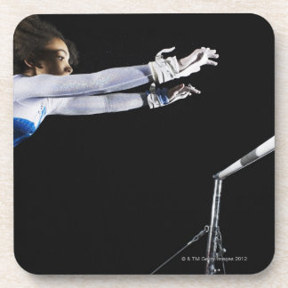 Gymnast (9-10) reaching for uneven bars 2 drink coasters