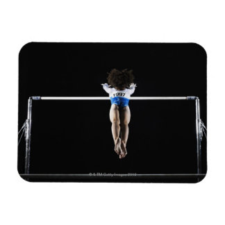 Gymnast (9-10) reaching for uneven bars magnet