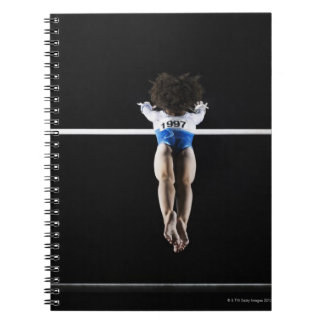 Gymnast (9-10) reaching for uneven bars note book