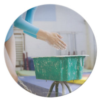 Gymnast chalking her hands party plates