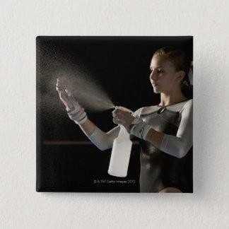 Gymnast spraying water on hands button